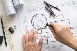Home inspection myth - looking at blue prints with a magnifying glass