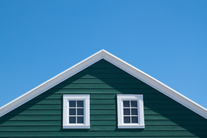 green sided home with white trim against a blue sky