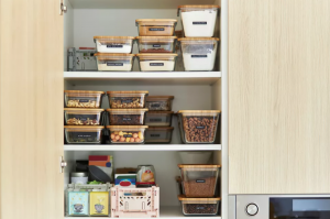kitchen storage solutions with glass food containers that are labeled and stacked comfortably in cupboard
